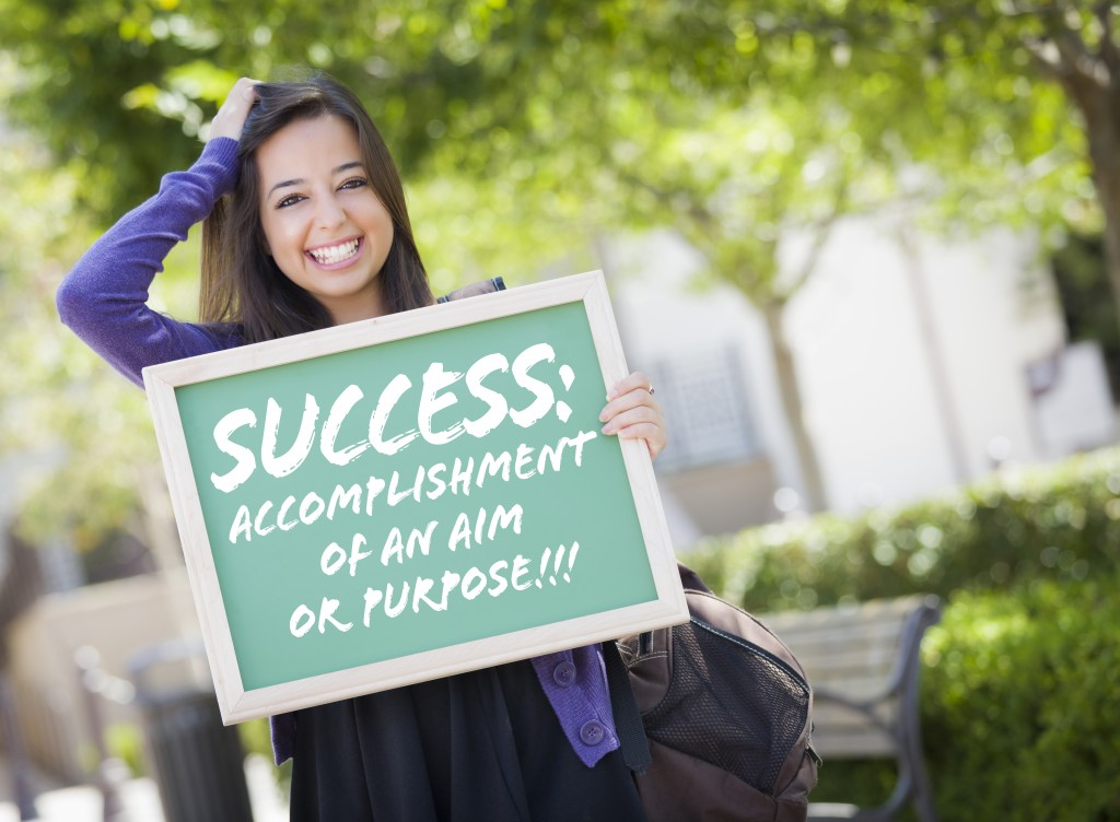 Excited Mixed Race Female Student Holding Chalkboard With Succes